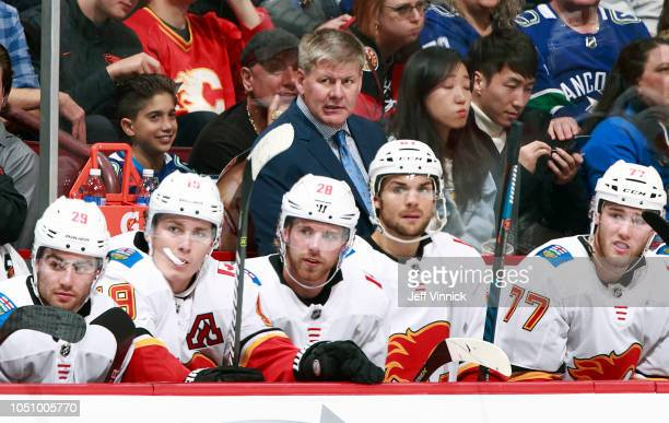 Head coach Bill Peters of the Calgary Flames looks on from the bench during their NHL game against the Vancouver Canucks at Rogers Arena October 3...