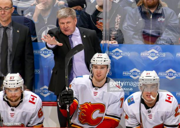 Head Coach Bill Peters of the Calgary Flames makes a point from the bench during third period action against the Winnipeg Jets at the Bell MTS Place...