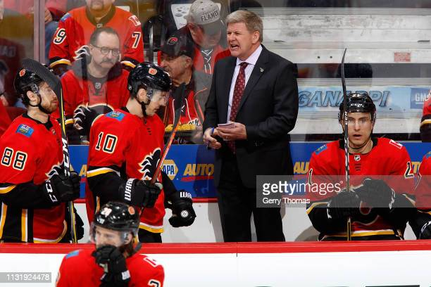Head coach Bill Peters of the Calgary Flames stands on the bench during an NHL game against the Ottawa Senators on March 21 2019 at the Scotiabank...