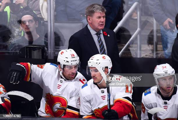 Head coach Bill Peters of the Calgary Flames watches play with James Neal and Mikael Backlund on the bench during the third period of the game...