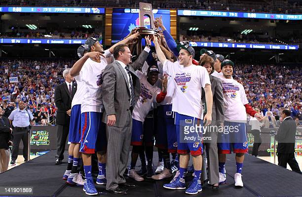 Head coach Bill Self of the Kansas Jayhawks celebrates with his players after receiving the trophy following their 80-67 win against the North...