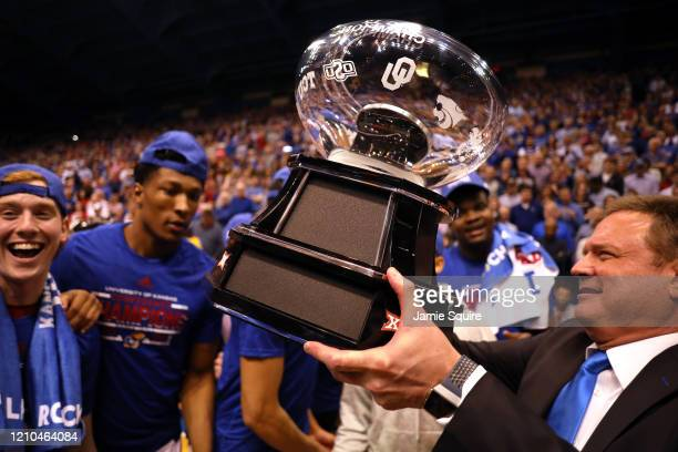 Head coach Bill Self of the Kansas Jayhawks hands the the Big 12 Championship Trophy to players after Kansas defeated the TCU Horned Frogs to win the...