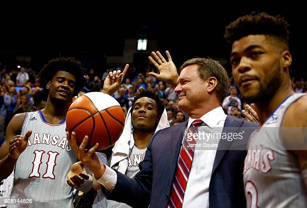 Head coach Bill Self of the Kansas Jayhawks is presented with a commemorative ball by players after being honored for his 600th win following the...