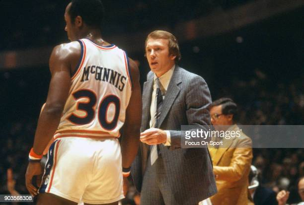 Head coach Billy Cunningham of the Philadelphia 76ers talks with his player George McGinnis while there's a break in the action of an NBA basketball...