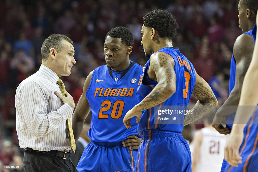 Head Coach Billy Donovan talks with Michael Frazier II #20 and Mike Rosario #3 of the Florida Gators during a game against the Arkansas Razorbacks at Bud Walton Arena on February 5, 2013 in Fayetteville, Arkansas. The Razorbacks defeated the Gators 80-69.