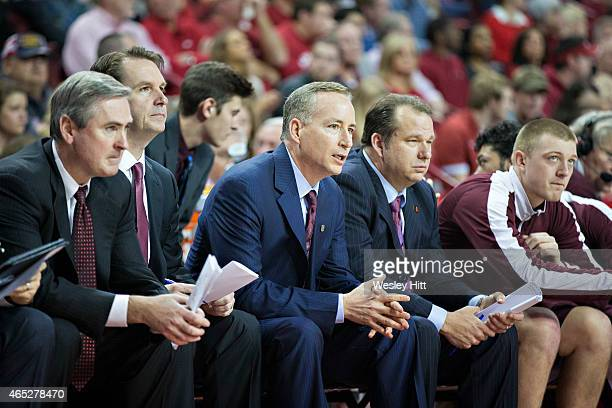Head Coach Billy Kennedy of the Texas AM Aggies on the bench with his assistant coaches during a game against the Arkansas Razorbacks at Bud Walton...
