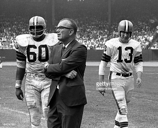 Head coach Blanton Collier of the Cleveland Browns looks towards the field after a play while offensive guard John Wooten and quarterback Frank Ryan...
