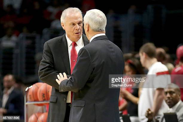 Head coach Bo Ryan of the Wisconsin Badgers talks with head coach Roy Williams of the North Carolina Tar Heels before the West Regional Semifinal of...