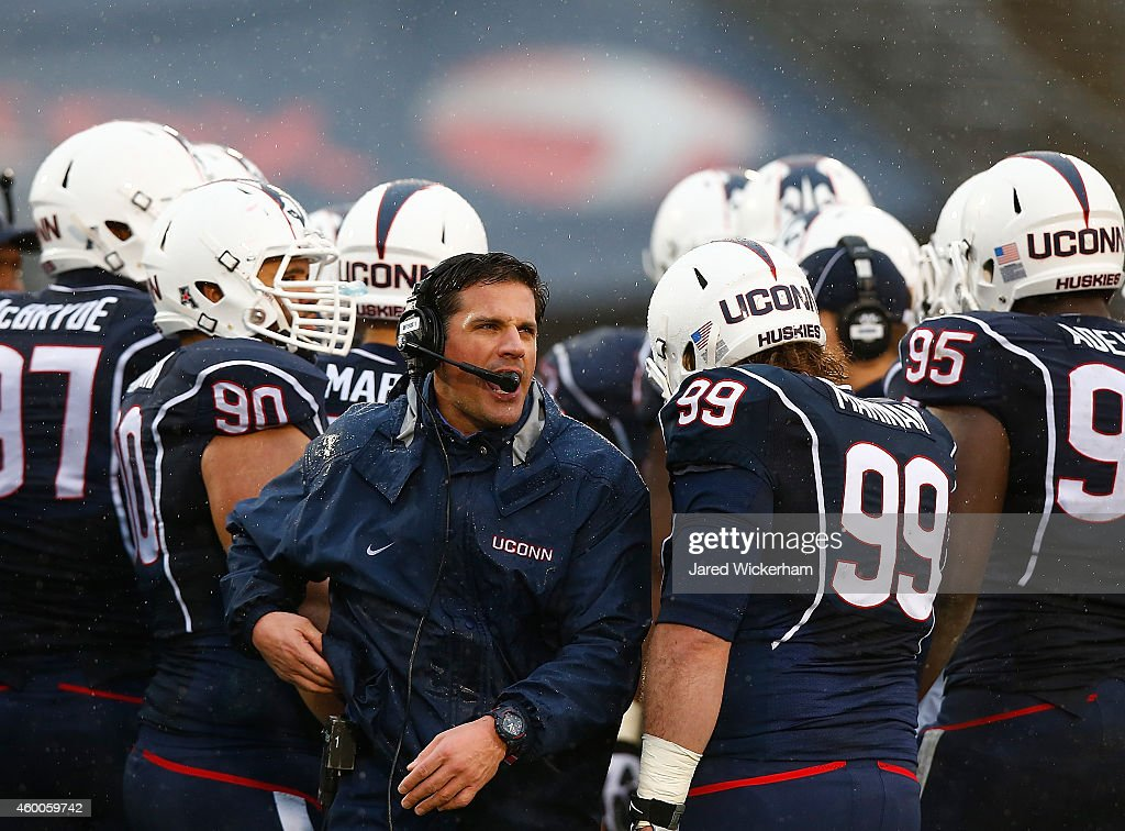 Head coach Bob Diaco of the Connecticut Huskies stands in a huddle during a timeout in the second half against the SMU Mustangs during the game at Rentschler Field on December 6, 2014 in East Hartford, Connecticut.