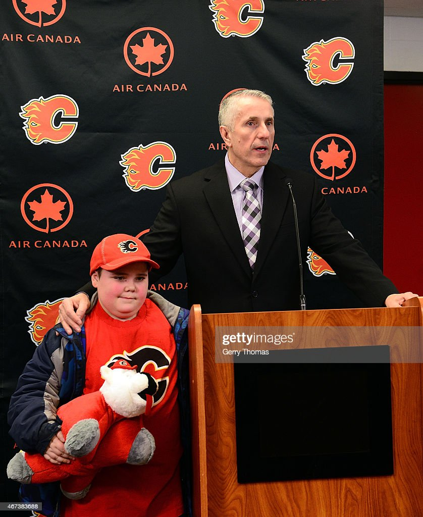 Head coach Bob Hartley of the Calgary Flames and a young fan speak to the media after a 3-2 win against the Colorado Avalanche at Scotiabank Saddledome on March 23, 2015 in Calgary, Alberta, Canada.