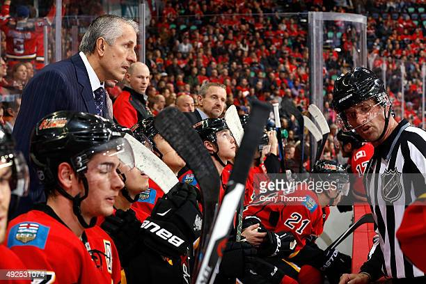 Head coach Bob Hartley of the Calgary Flames has a discussion with a referee during a stoppage in play against the St Louis Blues during an NHL game...