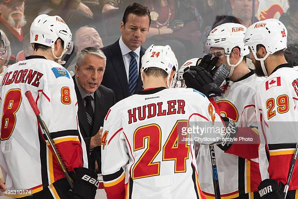 Head Coach Bob Hartley of the Calgary Flames talks to Joe Colborne x24n and Deryk Engelland during an NHL game against the Ottawa Senators at...