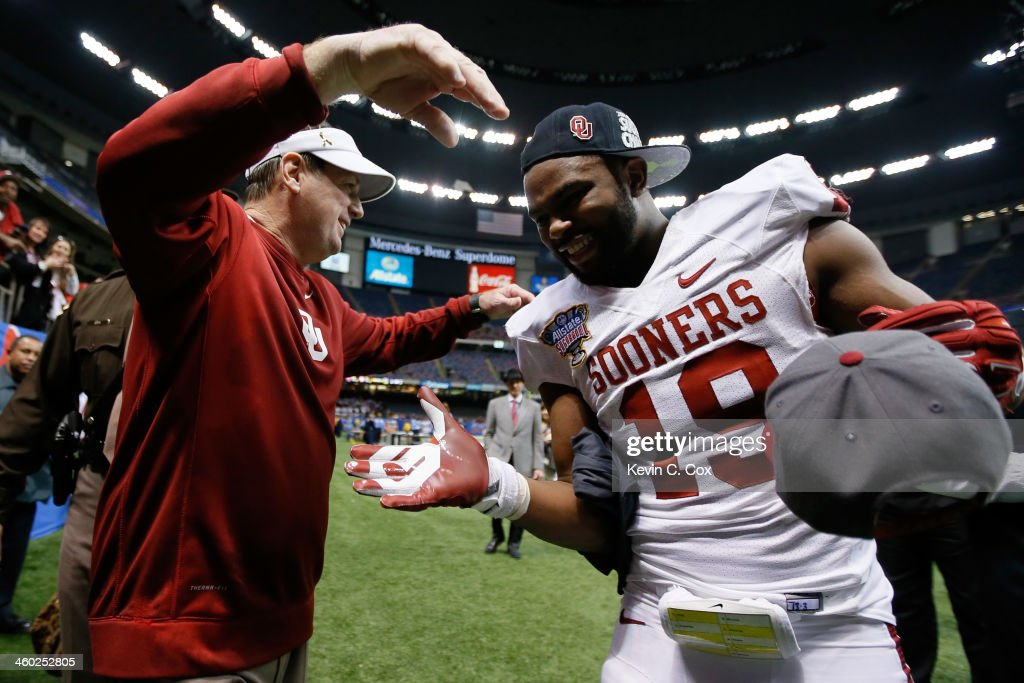 Head coach Bob Stoops celebrates with Eric Striker #19 of the Oklahoma Sooners after defeating the Crimson Tide 45-31 to win the Allstate Sugar Bowl at the Mercedes-Benz Superdome on January 2, 2014 in New Orleans, Louisiana.