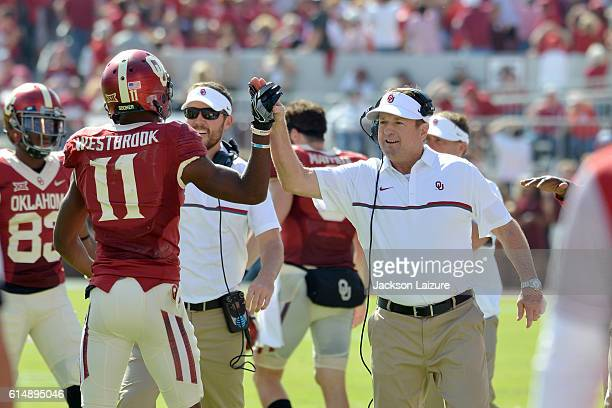 Head coach Bob Stoops congratulates wide receiver Dede Westbrook of the Oklahoma Sooners after a touchdown during their win against the Kansas State...