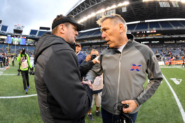 Head coach Bob Stoops of the Dallas Renegades left and head coach Jim Zorn of the Seattle Dragons right shake hands after the game at CenturyLink...