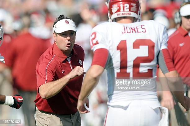 Head coach Bob Stoops of the Oklahoma Sooners congratulates quarterback Landry Jones after he threw a touchdown pass against the TCU Horned Frogs on...