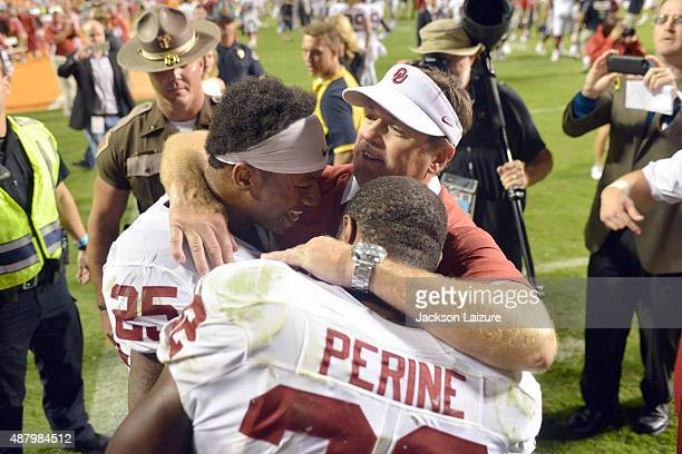 Head coach Bob Stoops of the Oklahoma Sooners hugs running backs Samaje Perine and Joe Mixon after an overtime victory against the Tennessee...