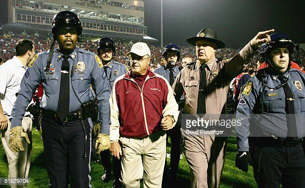 Head coach Bobby Bowden of the Florida State Seminoles is escorted off the field under guard after the Maryland Terrapins defeated the Florida State...