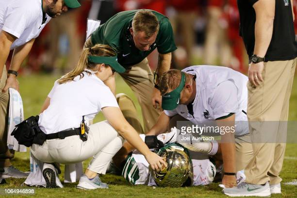 Head coach Brad Lambert looks on as the medical staff works on Alex Highsmith of the Charlotte 49ers after he was injured against the Florida...