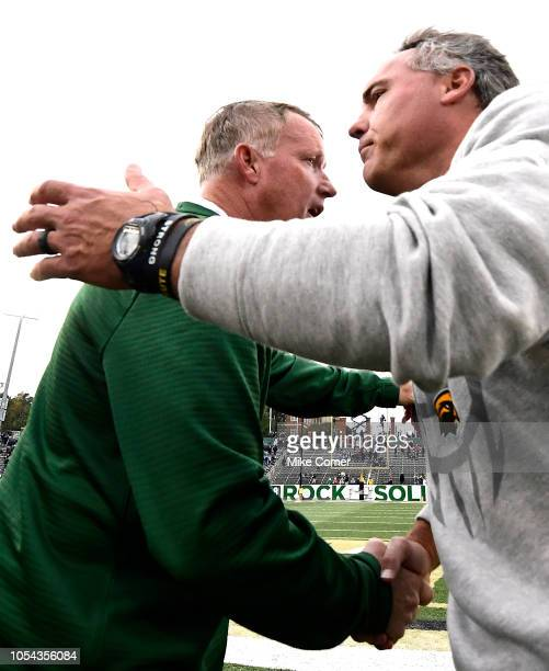 Head coach Brad Lambert of the Charlotte 49ers and head coach Jay Hopson of the Southern Miss Golden Eagles shake hands after 49ers beat the Golden...