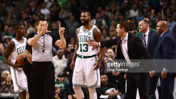 Head Coach Brad Stevens holds back Marcus Morris of the Boston Celtics after a call from the official during the second half of the game against the...