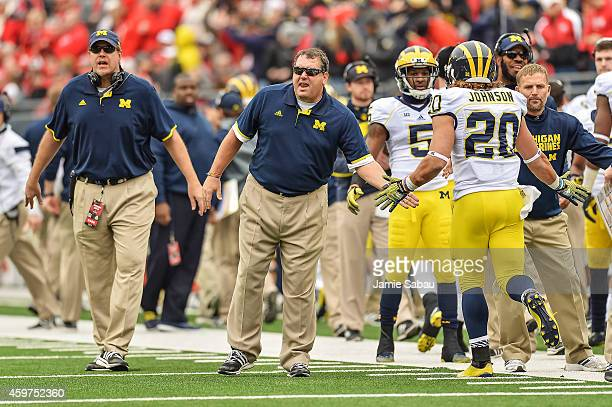 Head Coach Brady Hoke of the Michigan Wolverines congratulates his players as they come off the field against the Ohio State Buckeyes at Ohio Stadium...