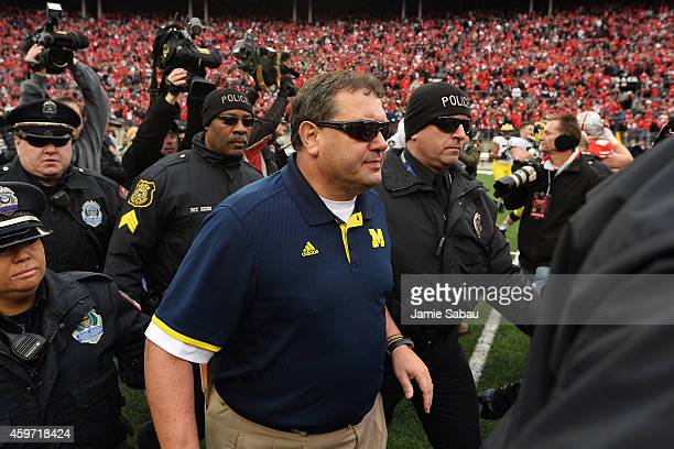 Head Coach Brady Hoke of the Michigan Wolverines is led off the field by security after his Wolverines lost to Ohio State 4228 at Ohio Stadium on...