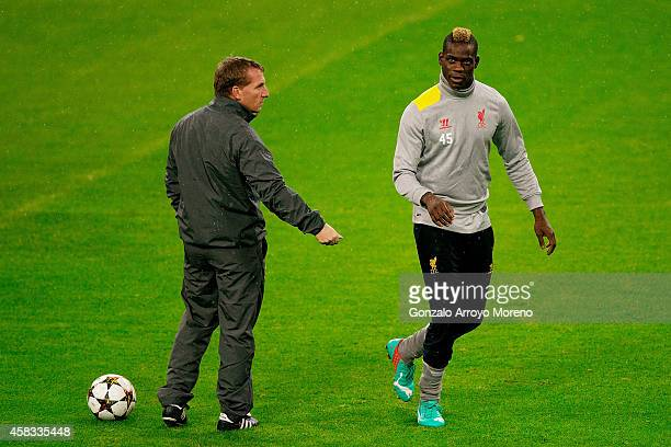 head coach Brendan Rodgers of Liverpool FC gives instructions to his player Mario Balotelli during the training session ahead of the UEFA Champions...