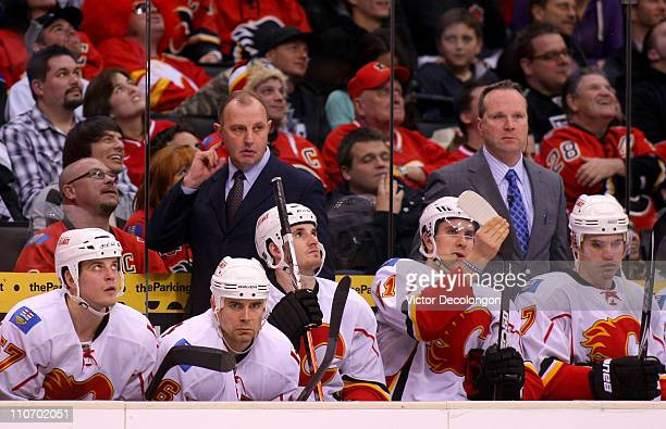 Head Coach Brent Sutter and Assistant Coach Dave Lowry of the Calgary Flames look on from behind the bench during their NHL game against the Los...