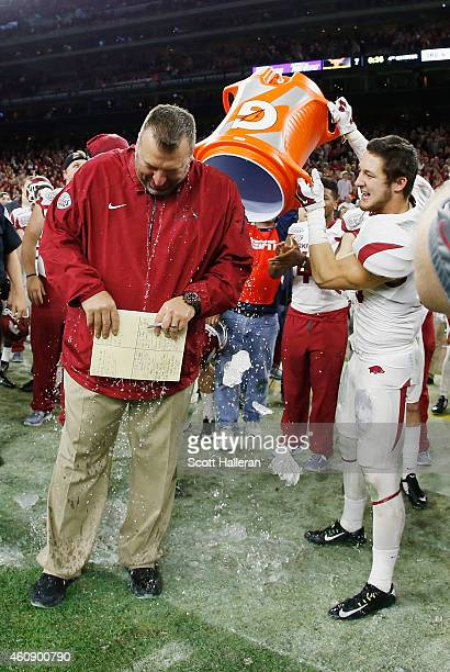 Head coach Bret Bielema of the Arkansas Razorbacks gets dunked by his player Drew Morgan after the Arkansas Razorbacks defeated the Texas Longhorns...