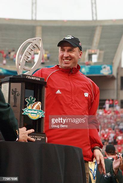 Head coach Bret Bielema of the Wisconsin Badgers smiles as he recieves the Capital One Bowl game trophy after winning against the Arkansas Razorbacks...