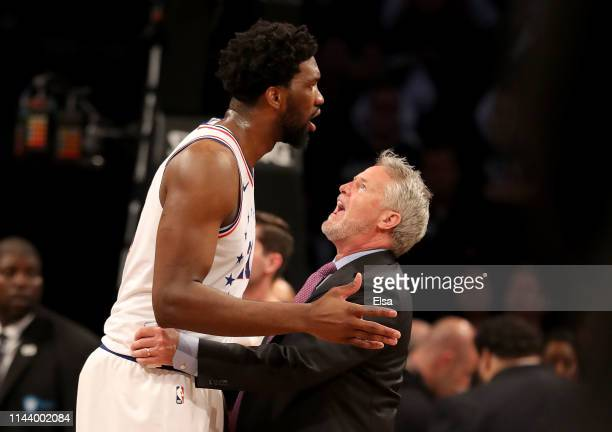 Head coach Brett Brown of the Philadelphia 76ers holds back his player Joel Embiid after a scuffle between Brooklyn Nets and Philadelphia 76ers...