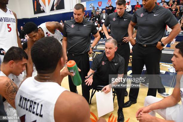 Head coach Brian Dutcher of the San Diego State Aztecs meets with his team during a time out in the championship game of the Wooden Legacy against...
