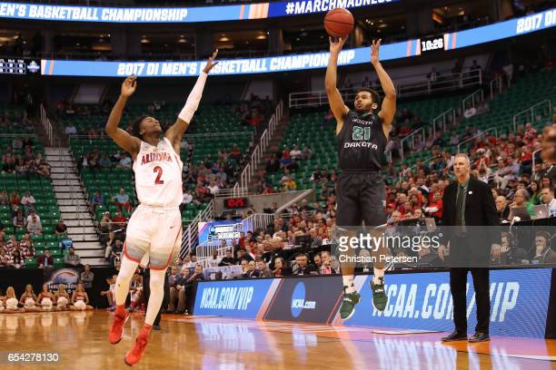 Head coach Brian Jones looks on as his player Quinton Hooker of the North Dakota Fighting Sioux attempts a shot defended by Kobi Simmons of the...