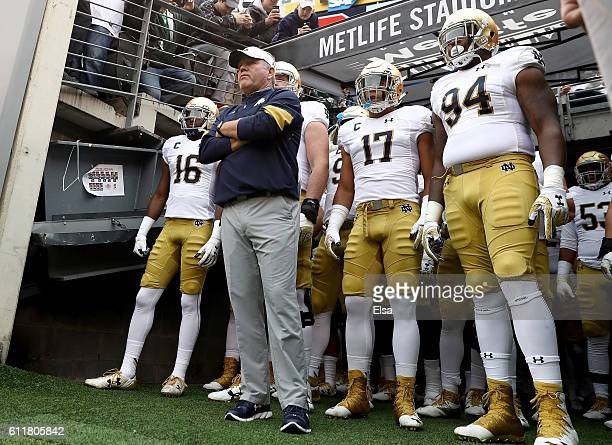 Head coach Brian Kelly of the Notre Dame Fighting Irish and his team wait to head on to the field for the start of the game against the Syracuse...