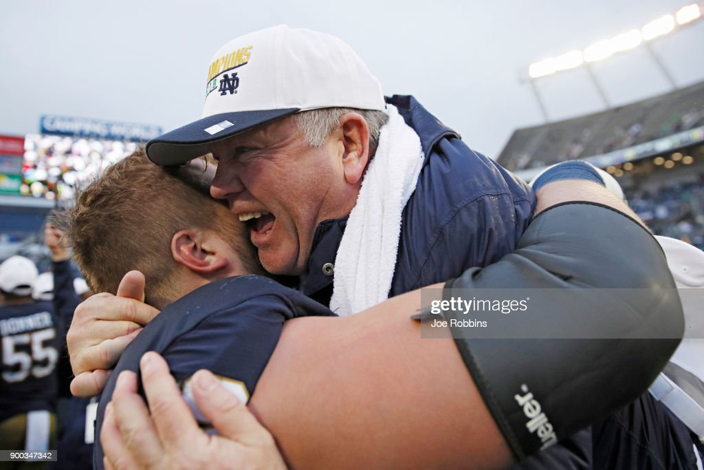 Head coach Brian Kelly of the Notre Dame Fighting Irish is lifted up by Hunter Bivin #70 following the Citrus Bowl against the LSU Tigers on January 1, 2018 in Orlando, Florida. Notre Dame won 21-17.