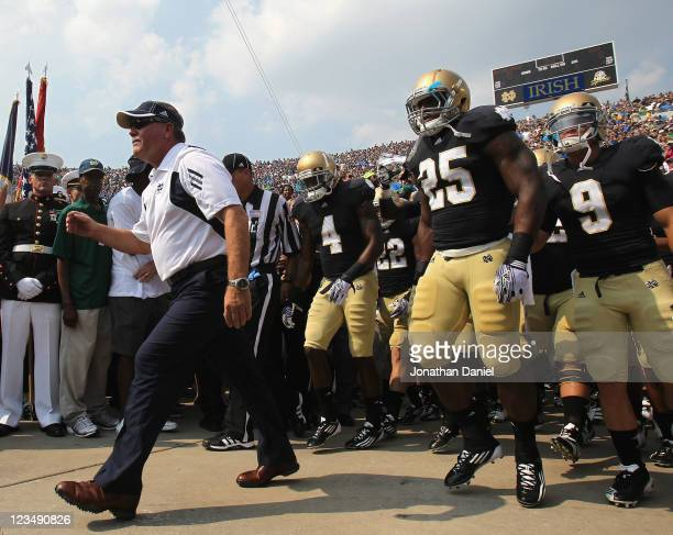 Head coach Brian Kelly of the Notre Dame Fighting Irish leads his team onto the field before taking on the University of South Florida Bulls at Notre...