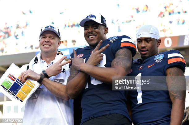 Head coach Bronco Mendenhall Chris Peace and Jordan Ellis of the Virginia Cavaliers celebrate after a win against the South Carolina Gamecocks during...