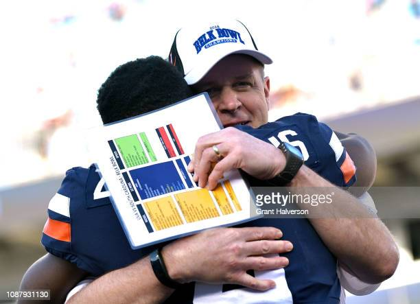Head coach Bronco Mendenhall hugs Olamide Zaccheaus of the Virginia Cavaliers after a win against the South Carolina Gamecocks during the Belk Bowl...