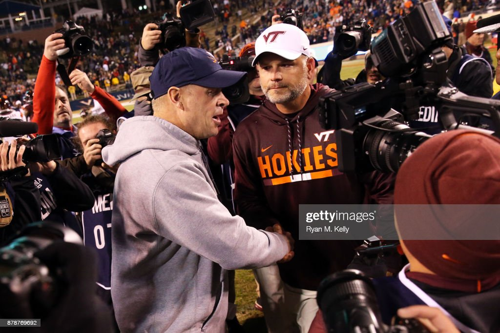 Head coach Bronco Mendenhall of the Virginia Cavaliers and head coach Justin Fuente of the Virginia Tech Hokies shake hands after a game at Scott Stadium on November 24, 2017 in Charlottesville, Virginia. Virginia Tech defeated Virginia 10-0.