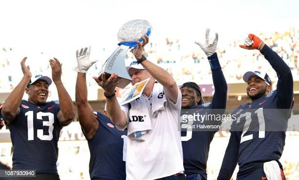 Head coach Bronco Mendenhall of the Virginia Cavaliers celebrates with the trophy after a win against the South Carolina Gamecocks during the Belk...