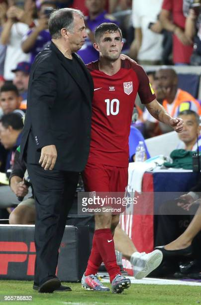 USA head coach Bruce Arena puts his arm around player Christian Pulisic during action against Panama during World Cup qualifier match at Orlando City...