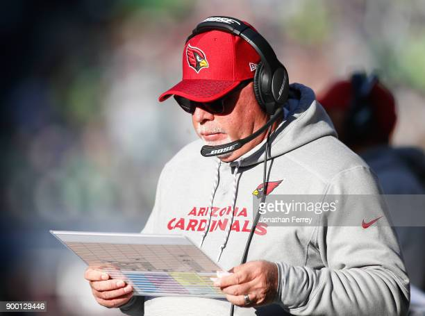 Head coach Bruce Arians of the Arizona Cardinals looks over plays during the game against the Seattle Seahawks at CenturyLink Field on December 31...