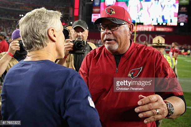 Head coach Bruce Arians of the Arizona Cardinals shakes hands with Pete Carroll of the Seattle Seahawks following the NFL game at the University of...