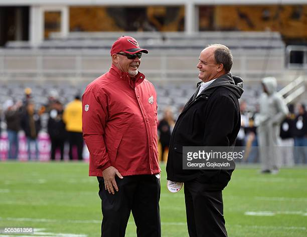 Head coach Bruce Arians of the Arizona Cardinals talks to general manager Kevin Colbert of the Pittsburgh Steelers before a game at Heinz Field on...