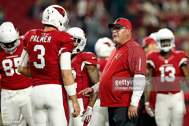 Head coach Bruce Arians of the Arizona Cardinals talks with quarterback Carson Palmer before the Cardinals take on the Green Bay Packers in the NFC...