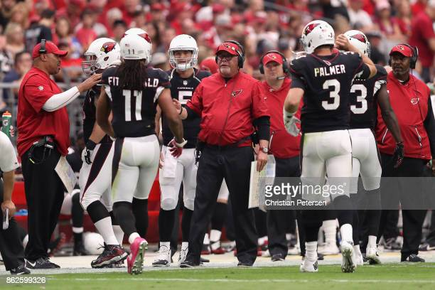 Head coach Bruce Arians of the Arizona Cardinals talks with wide receiver Larry Fitzgerald and quarterback Carson Palmer during the first half of the...