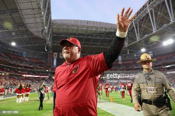 Head coach Bruce Arians of the Arizona Cardinals waves to fans as he walks off the field following the NFL game against the New York Giants at the...