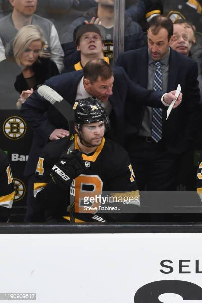 Head coach Bruce Cassidy and Jake DeBrusk of the Boston Bruins talk during the third period against the Buffalo Sabres at the TD Garden on December...