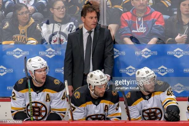 Head Coach Bruce Cassidy David Backes Patrice Bergeron and David Krejci of the Boston Bruins look on from the bench during third period action...